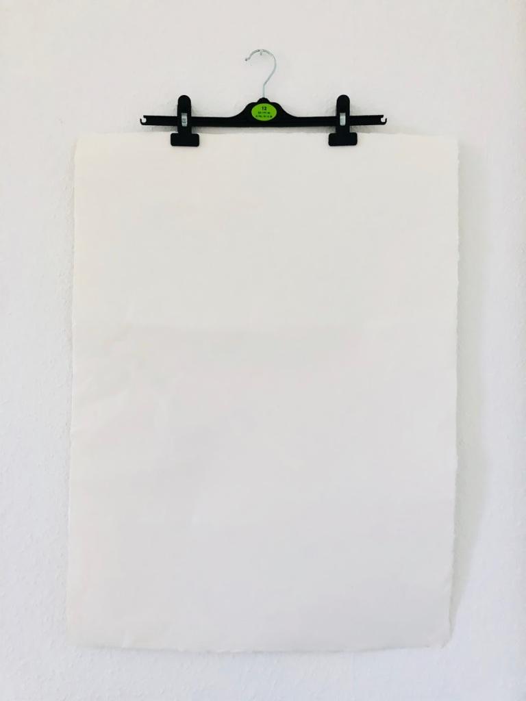 Eine Fotografie der Installation Spaceholder. Zu sehen ist ein Aquarellpapier, das an einem Bügel befestigt an der Wand hängt.